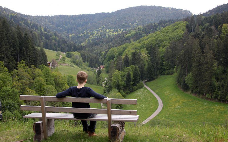 Jung sitzt auf einer Sitzbank und blickt ins hintere Zuwälder Tal