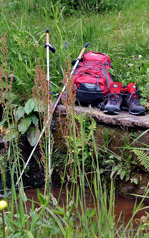 Wanderrucksack und Wanderschuhe am der Wassertretstelle